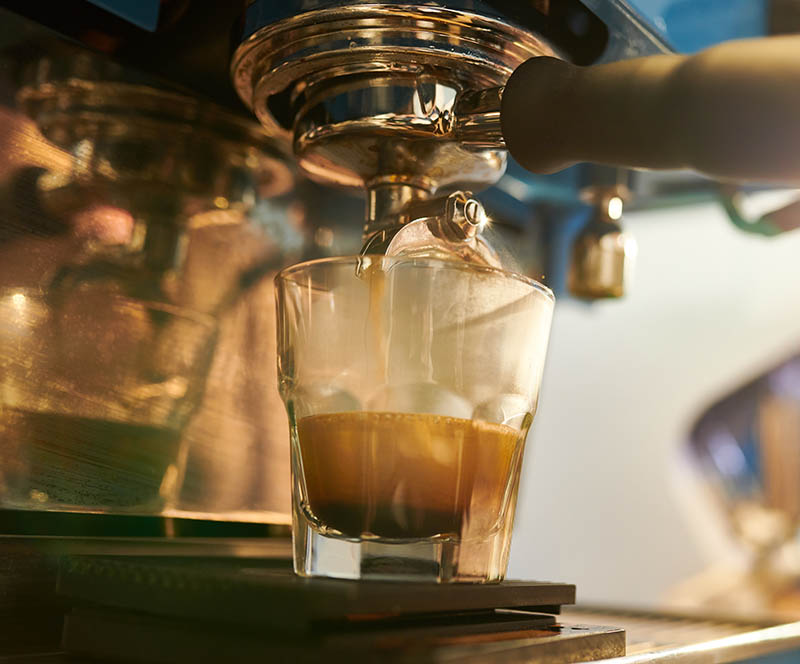Glass in coffee machine and hot aromatic espresso or cappuccino pouring down for client
